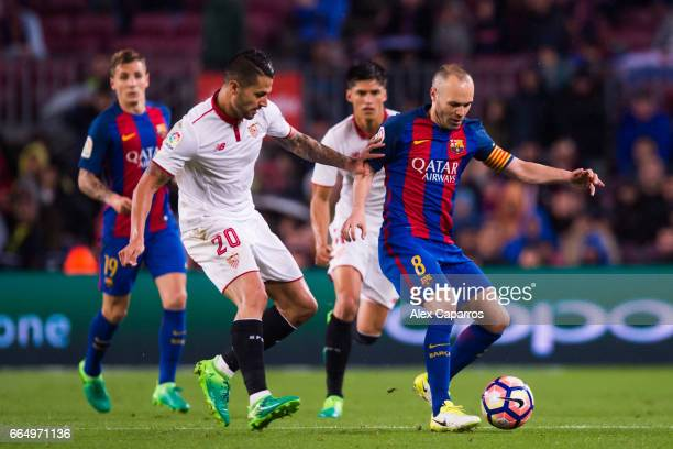 Andres Iniesta of FC Barcelona conducts the ball past Victor Machin 'Vitolo' of Sevilla FC during the La Liga match between FC Barcelona and Sevilla...