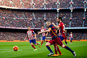 Andres Iniesta of FC Barcelona conducts the ball under a challenge of Juanfran Torres of Club Atletico de Madrid during the La Liga match between FC...