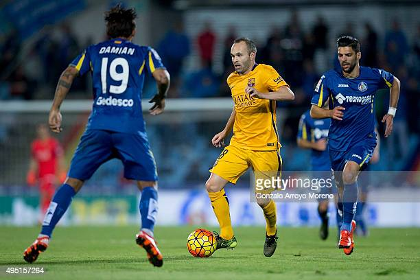 Andres Iniesta of FC Barcelona controls the ball between Angel Lafita of Getafe CF and his teammate Damian Suarez during the La Liga match between...