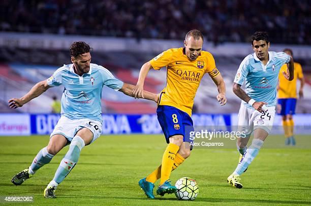 Andres Iniesta of FC Barcelona controls the ball between Sergi Gomez and Augusto Fernandez of Celta Vigo during the La Liga match between Celta Vigo...