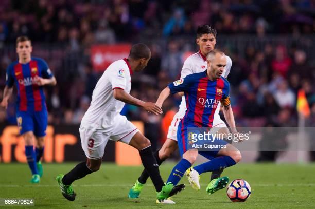 Andres Iniesta of FC Barcelona dribbles Mariano Ferreira and Joaquin Correa of Sevilla FC during the La Liga match between FC Barcelona and Sevilla...