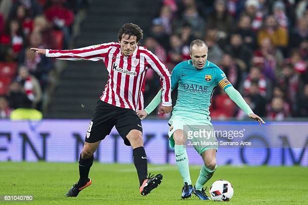Andres Iniesta of FC Barcelona duels for the ball with Ander Iturraspe of Athletic Club during the Copa del Rey Round of 16 first leg match between...