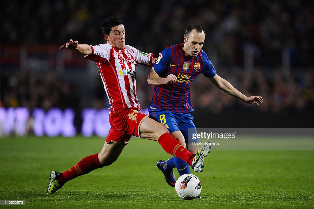 Andres Iniesta of FC Barcelona (R) duels for the ball with Andre Castro of Sporting de Gijon during the La Liga match between FC Barcelona and Sporting Gijon at Camp Nou on March 3, 2012 in Barcelona, Spain.