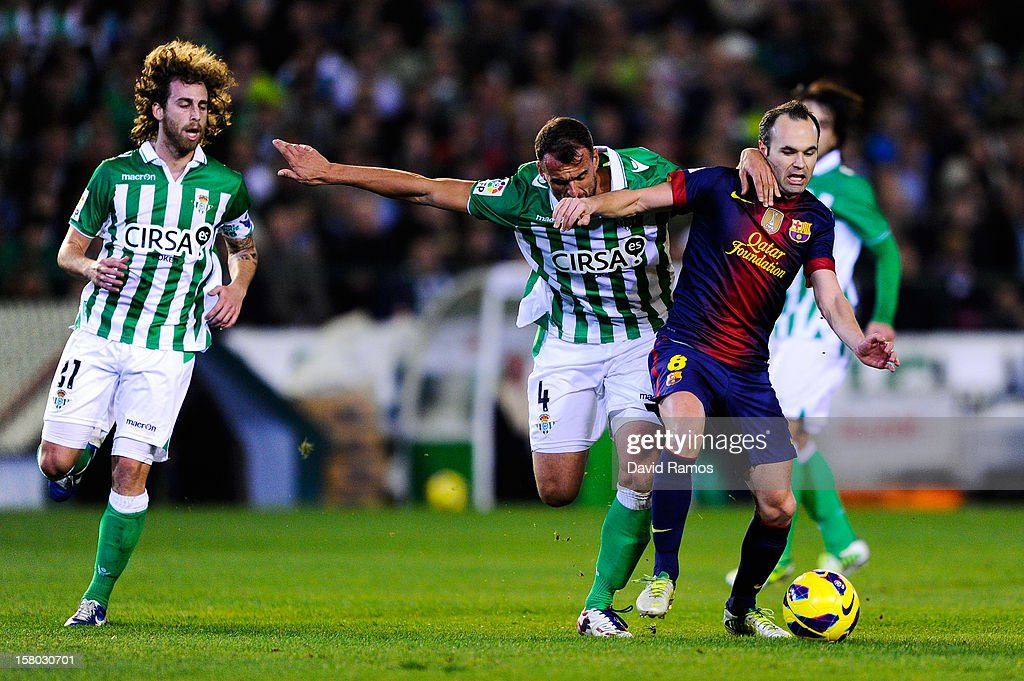Andres Iniesta of FC Barcelona duels for the ball with Antonio Amaya of Real Betis Balompie during the La Liga match between Real Betis Balompie and FC Barcelona at Estadio Benito Villamarin on December 9, 2012 in Seville, Spain.