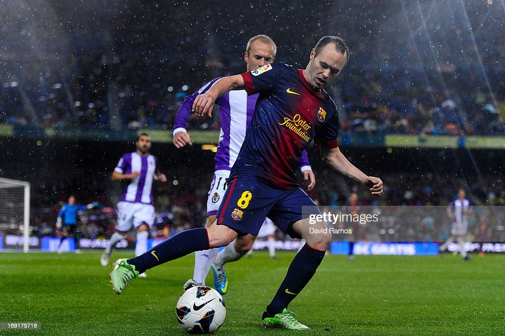 Andres Iniesta of FC Barcelona duels for the ball with Daniel Larsson of Real Valladolid CF during the La Liga match between FC Barcelona and Real Valladolid CF at Camp Nou on May 19, 2013 in Barcelona, Spain.
