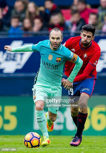 Andres Iniesta of FC Barcelona duels for the ball with Kenan Kodro of CA Osasuna during the La Liga match between CA Osasuna and FC Barcelona at...