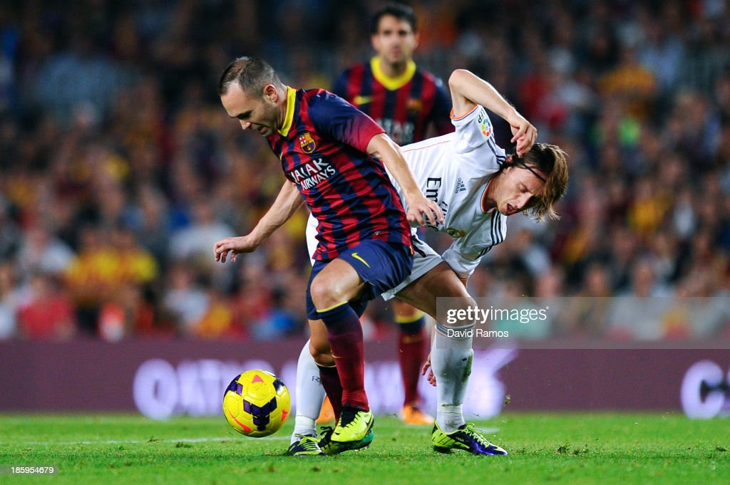 Andres Iniesta of FC Barcelona (L) duels for the ball with Luka Modric of Real Madrid CF during the La Liga match between FC Barcelona and Real Madrid CF at Camp Nou on October 26, 2013 in Barcelona, Spain.