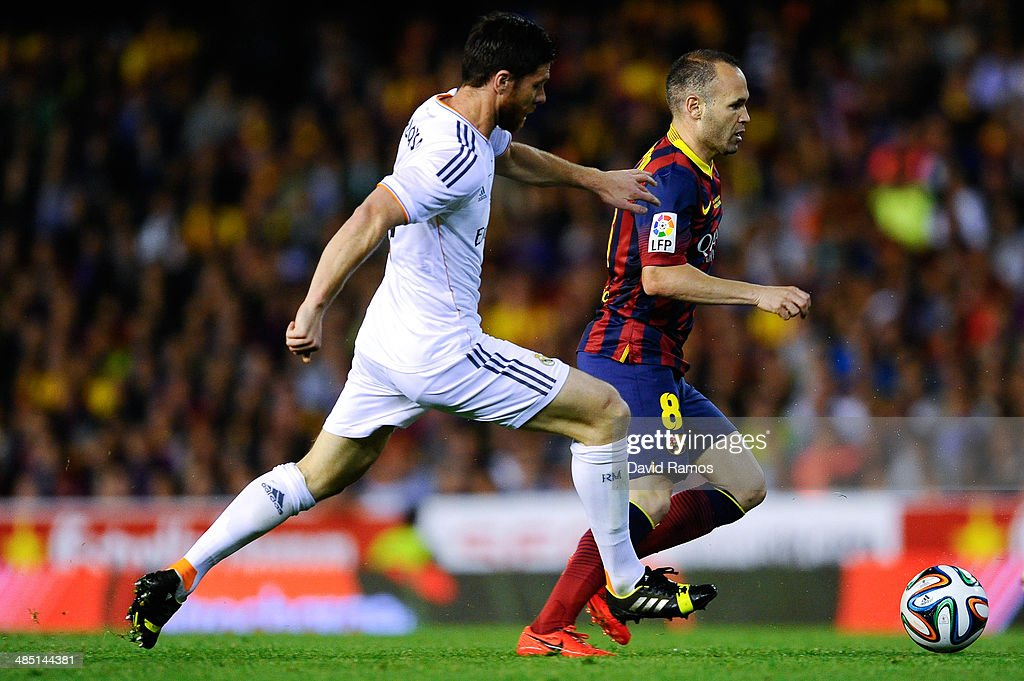 Andres Iniesta of FC Barcelona duels for the ball with Xabi Alonso of Real Madrid CF during the Copa del Rey Final between Real Madrid and FC Barcelona at Estadio Mestalla on April 16, 2014 in Valencia, Spain.