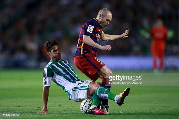 Andres Iniesta of FC Barcelona is tackled by Alvaro Cejudo of Real Betis Balompie during the La Liga match between Real Betis Balompie and FC...