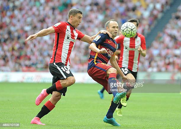 Andres Iniesta of FC Barcelona is tackled by Oscar de Marcos of Athletic Club during the La Liga match between Athletic Club and FC Barcelona at San...