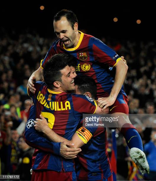 Andres Iniesta of FC Barcelona jumps over his teammates Gerard Pique and David Villa after Pique scored their team's third goal during the UEFA...