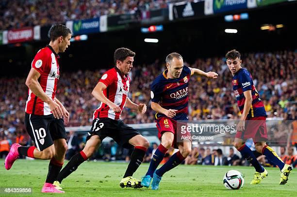 Andres Iniesta of FC Barcelona runs with the ball past Oscar de Marcos and Gorka Elustondo of Athletic Club and his teammate Munir El Haddadi during...