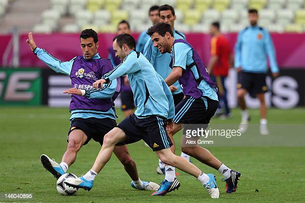 Andres Iniesta of Spain is challenged by Sergio Busquets and Javi Martinezduring a UEFA EURO 2012 training session ahead of their Group C match...