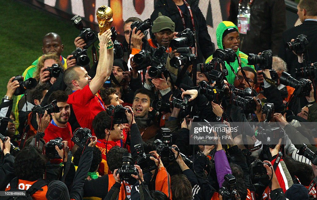 Andres Iniesta of Spain is surrounded by photographers as he celebrates with the World Cup after the 2010 FIFA World Cup South Africa Final match between Netherlands and Spain at Soccer City Stadium on July 11, 2010 in Johannesburg, South Africa.
