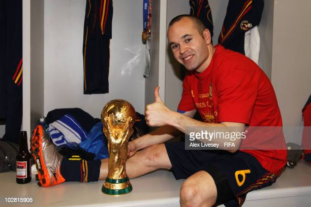 Andres Iniesta of Spain poses with the trophy in the Spanish dressing room after they won the 2010 FIFA World Cup at Soccer City Stadium on July 11...