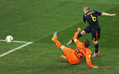 Andres Iniesta of Spain scores the opening goal as Rafael Van der Vaart of the Netherlands tries to defend during the 2010 FIFA World Cup South...