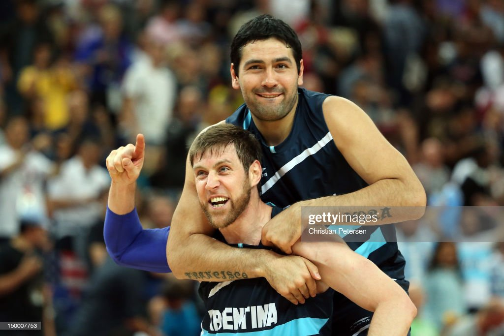Andres Nocioni #13 and Martin Leiva #12 of Argentina celebrate Argentina's 82-77 victory against Brazil during the Men's Basketball quaterfinal game on Day 12 of the London 2012 Olympic Games at North Greenwich Arena on August 8, 2012 in London, England.