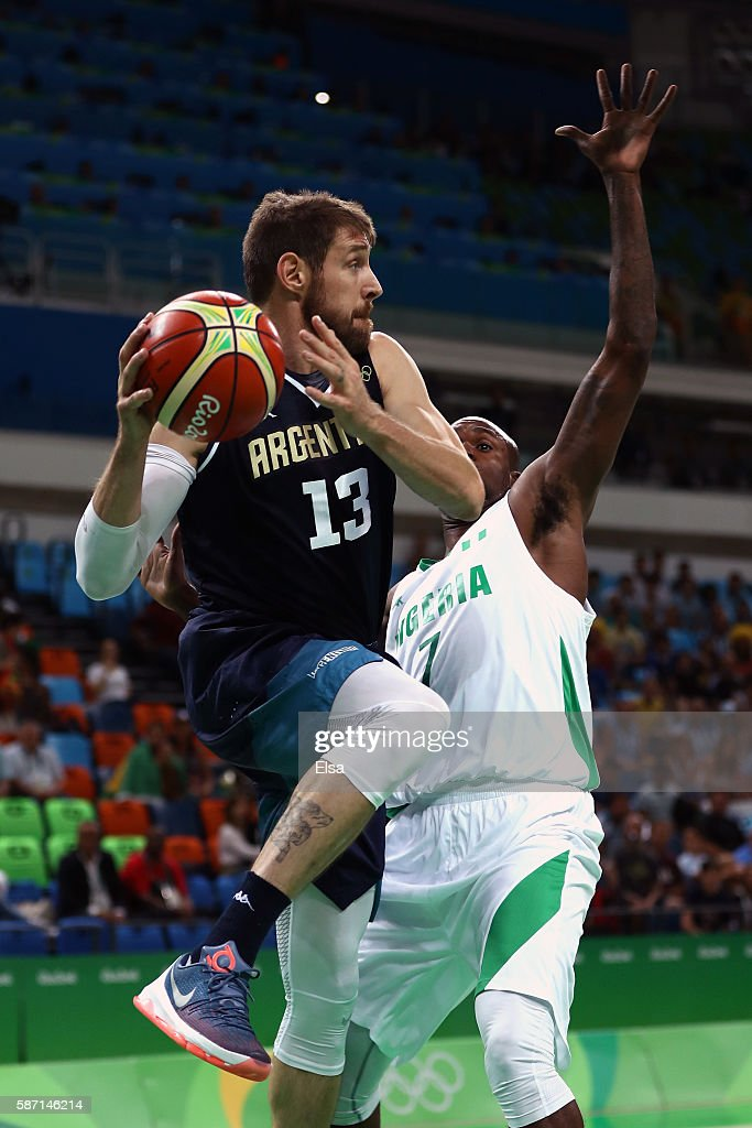 Andres Nocioni of Argentina drives the ball against AlFarouq Aminu of Nigeria during a Men's preliminary round basketball game between Nigeria and...