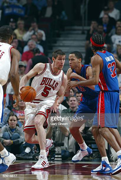 Andres Nocioni of the Chicago Bulls dribbles the ball as Tayshaun Prince of the Detroit Pistons guards and Richard Hamilton watches on April 11 2005...