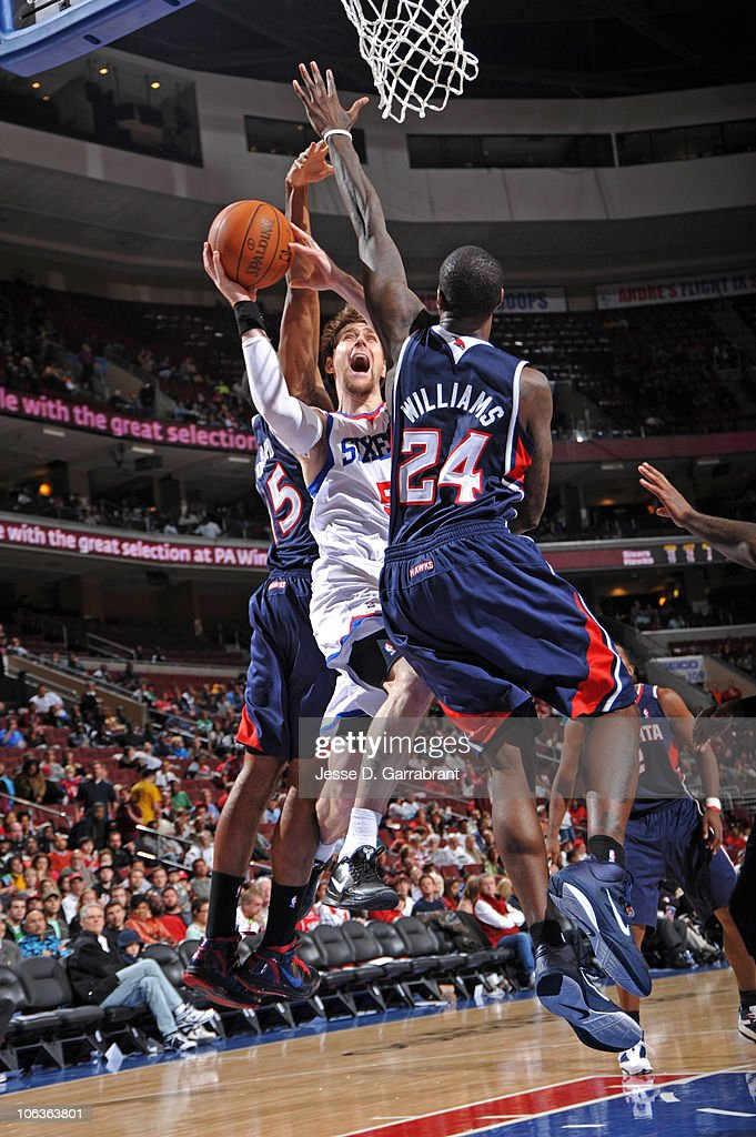 Andres Nocioni #5 of the Philadelphia 76ers shoots against <a gi-track='captionPersonalityLinkClicked' href=/galleries/search?phrase=Al+Horford&family=editorial&specificpeople=699030 ng-click='$event.stopPropagation()'>Al Horford</a> #15 and <a gi-track='captionPersonalityLinkClicked' href=/galleries/search?phrase=Marvin+Williams&family=editorial&specificpeople=206784 ng-click='$event.stopPropagation()'>Marvin Williams</a> #24 of the Atlanta Hawks during the game on October 29, 2010 at the Wells Fargo Center in Philadelphia, Pennsylvania.