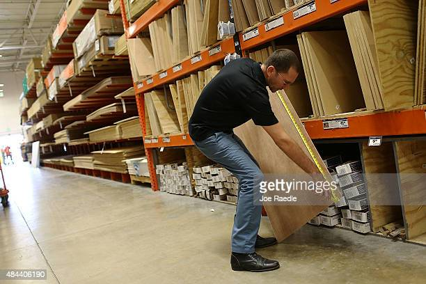 Andres Perez measures a piece of plywood at a Home Depot on August 18 2015 in Miami Florida Today Home Depot shares rose as the company reported...