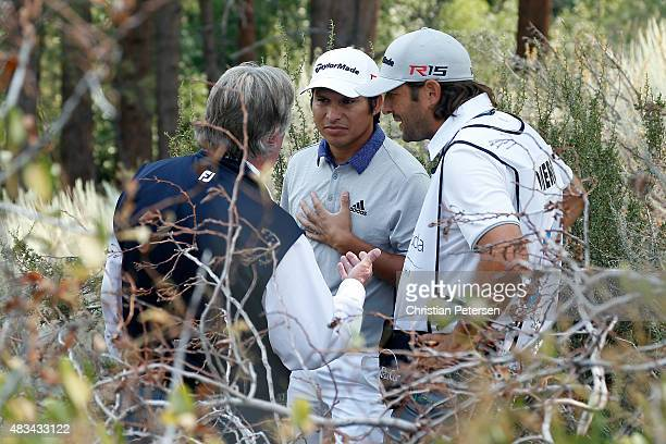 Andres Romero and his caddie Angel Monguzzi talk with PGA Tour Chief referee Mark Russell after Romero withdrew due to a hand injury in the third...
