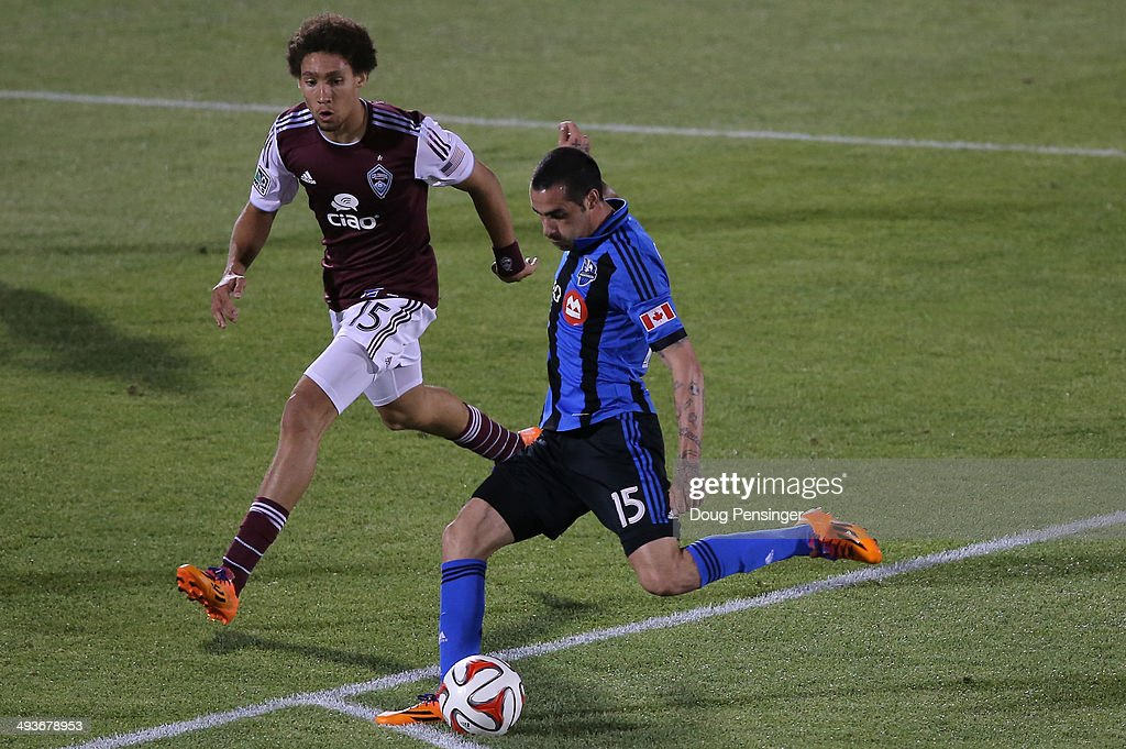 Andres Romero #15 of the Montreal Impact strikes the ball for a goal in the 88th minute against Chris Klute #15 of the Colorado Rapids at Dick's Sporting Goods Park on May 24, 2014 in Commerce City, Colorado. The Rapids defeated the Impact 4-1.