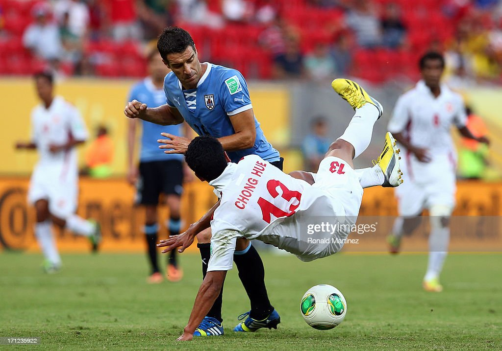 Andres Scotti of Uruguay battles for the ball with Steevy Chong Hue of Tahiti during the FIFA Confederations Cup Brazil 2013 Group B match between Uruguay and Tahiti at Arena Pernambuco on June 22, 2013 in Recife, Brazil.