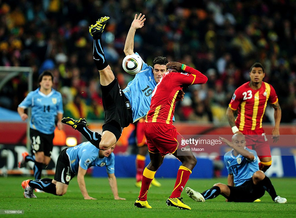 Andres Scotti of Uruguay challenges for a high ball above Asamoah Gyan of Ghana during the 2010 FIFA World Cup South Africa Quarter Final match...