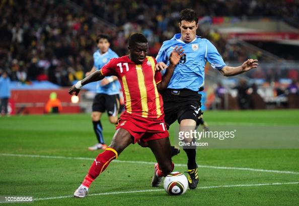 Andres Scotti of Uruguay challenges Sulley Muntari of Ghana during the 2010 FIFA World Cup South Africa Quarter Final match between Uruguay and Ghana...