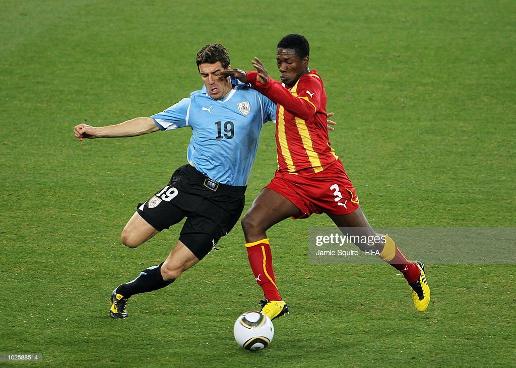 Andres Scotti of Uruguay tackles Asamoah Gyan of Ghana during the 2010 FIFA World Cup South Africa Quarter Final match between Uruguay and Ghana at...