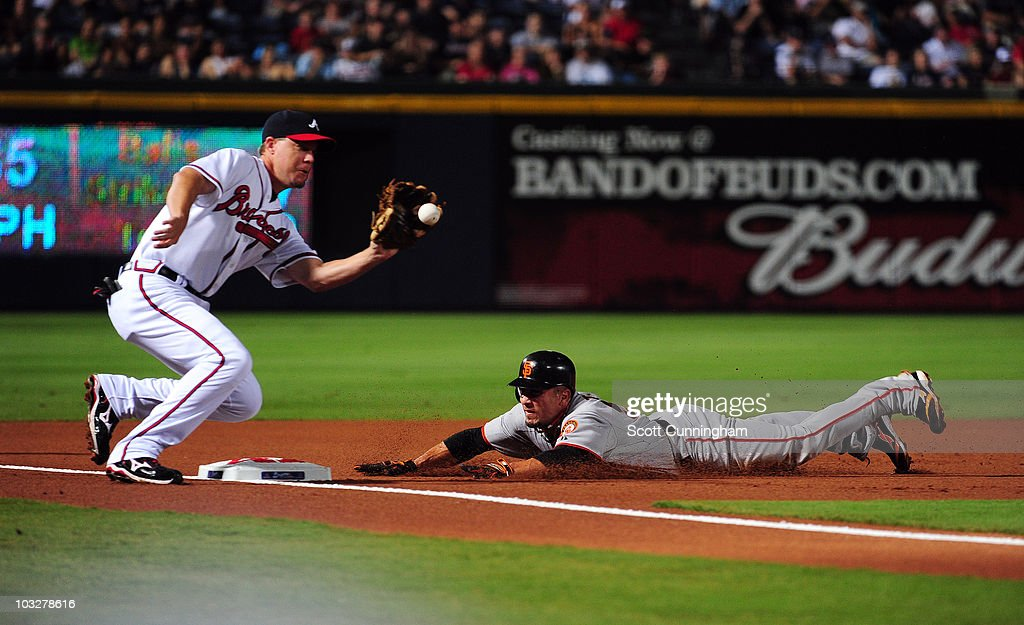 Andres Torres #56 of the San Francisco Giants dives in safely to third base under the tag of Chipper Jones #10 of the Atlanta Braves at Turner Field on August 6, 2010 in Atlanta, Georgia. The Giants defeated the Braves 3-2.