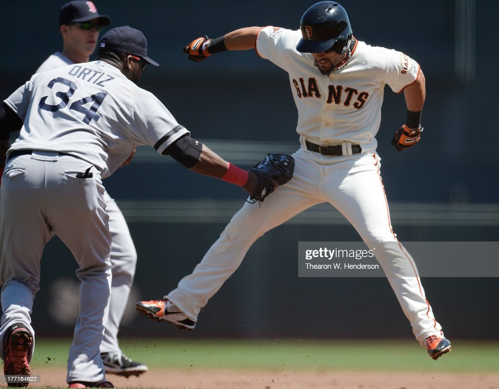 Andres Torres of the San Francisco Giants gets caught in a rundown between first and second base tagged out by David Ortiz of the Boston Red Sox in...