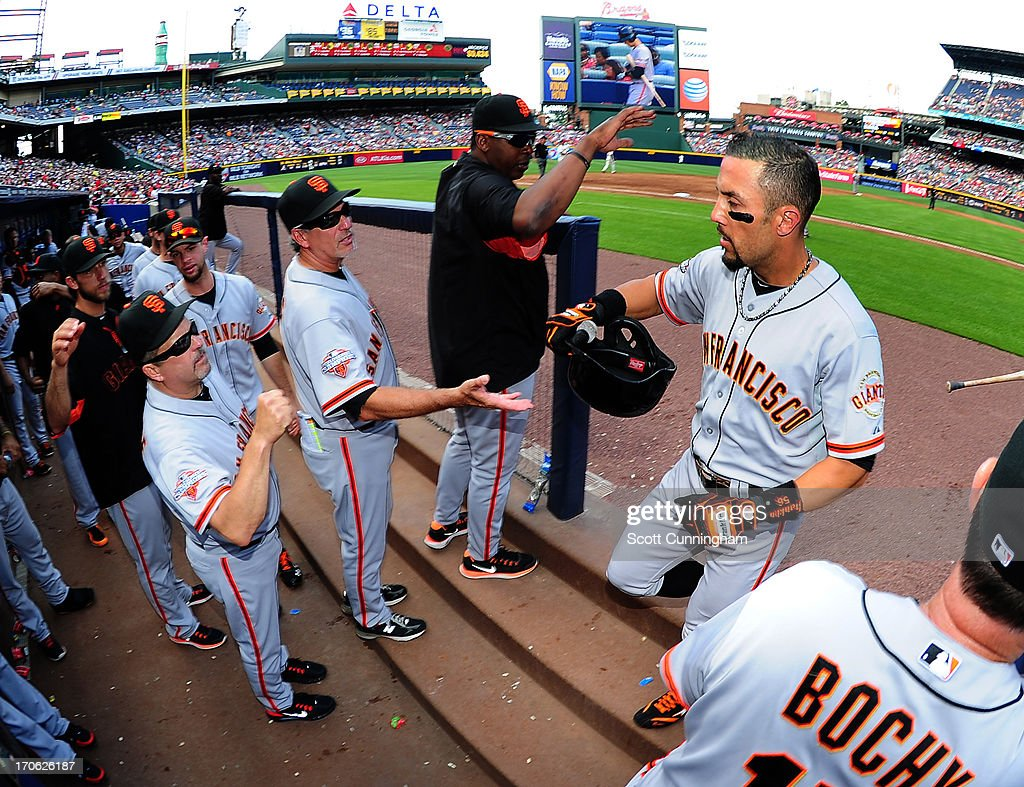 Andres Torres #56 of the San Francisco Giants is congratulated by teammates after scoring against the Atlanta Braves at Turner Field on June 15, 2013 in Atlanta, Georgia.