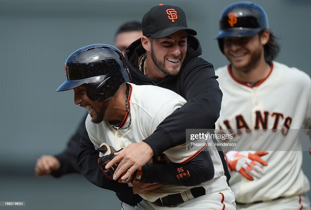 Andres Torres #56 of the San Francisco Giants is hugged by George Kontos #70 after Torres hit an RBI walk-off single scoring Buster Posey #28 (not pictured) to defeat the Philadelphia Phillies 4-3 in the bottom of the 10th inning at AT&T Park on May 8, 2013 in San Francisco, California.