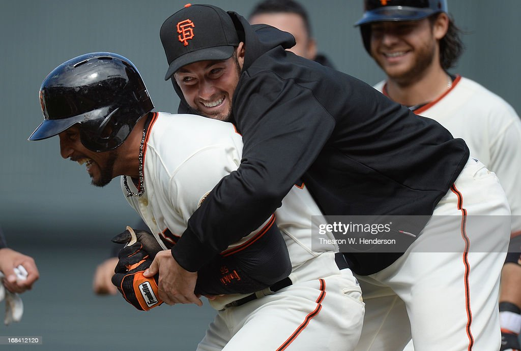 Andres Torres of the San Francisco Giants is hugged by George Kontos after Torres hit an RBI walkoff single scoring Buster Posey to defeat the...