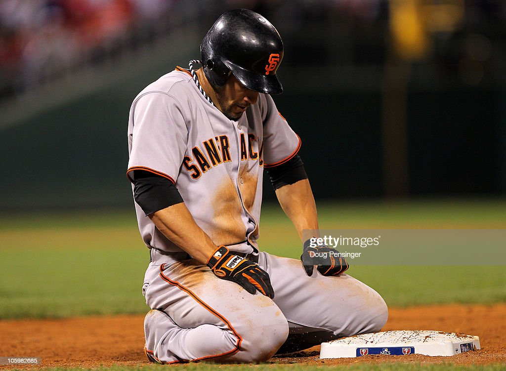 Andres Torres of the San Francisco Giants kneels after diving back to first base for a single against the Philadelphia Phillies in Game Six of the...