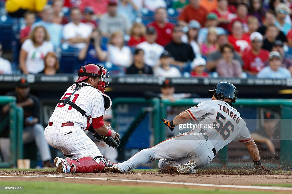 Andres Torres of the San Francisco Giants safely slides into home to score a run past Carlos Ruiz of the Philadelphia Phillies in the first inning of...