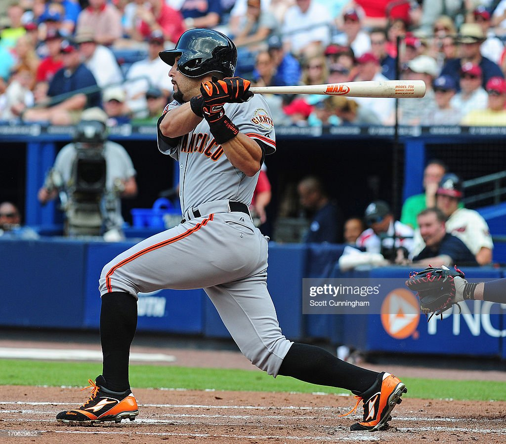 Andres Torres of the San Francisco Giants singles to knock in a run against the Atlanta Braves at Turner Field on June 15 2013 in Atlanta Georgia