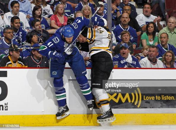 Andrew Alberts of the Vancouver Canucks gets checked by Dennis Seidenberg of the Boston Bruins in Game Two of the 2011 NHL Stanley Cup Finals at...