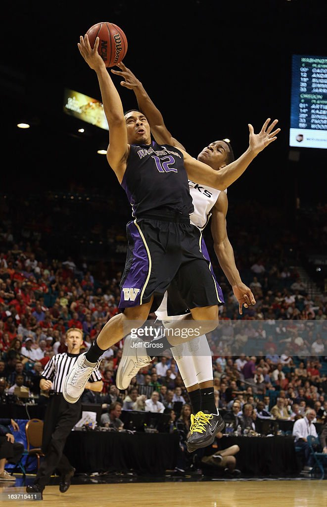 Andrew Andrews #12 of the Washington Huskies is fouled in the act of shooting by Dominic Artis #1 of the Oregon Ducks in the first half during the quarterfinals of the Pac 12 Basketball Tournament at the MGM Grand Garden Arena on March 14, 2013 in Las Vegas, Nevada.