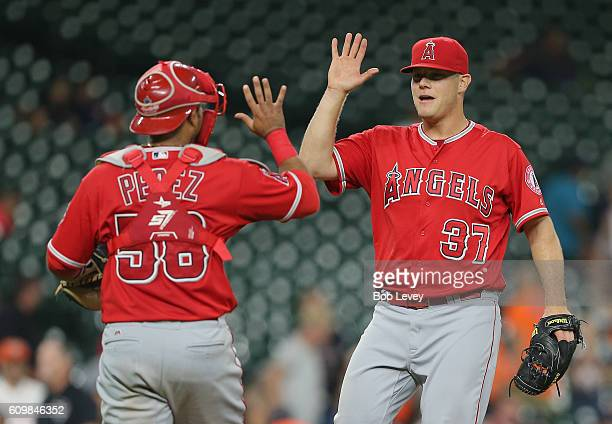 Andrew Bailey of the Los Angeles Angels of Anaheim high fives catcher Carlos Perez after the final out against the Houston Astros at Minute Maid Park...