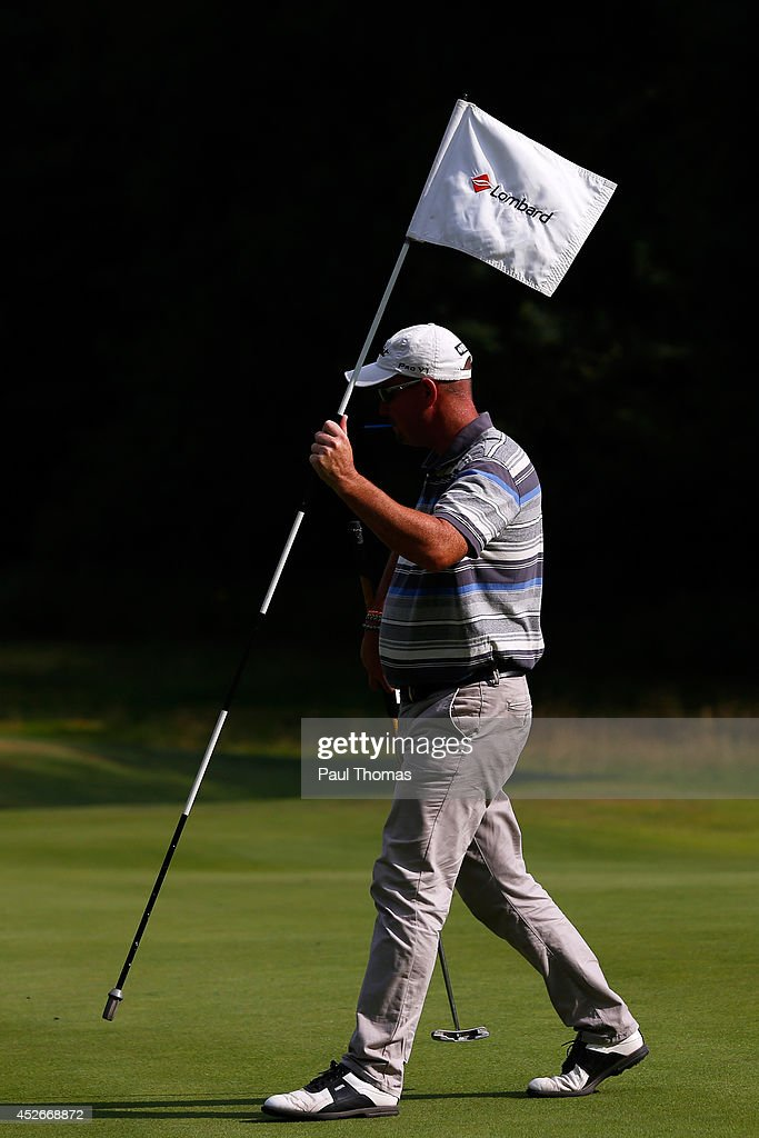 Andrew Barnett of Pennant Park Golf Club carries the pin flag during The Lombard Trophy North West Regional Qualifier at Dunham Forest Golf Club on July 25, 2014 in Altrincham, England.