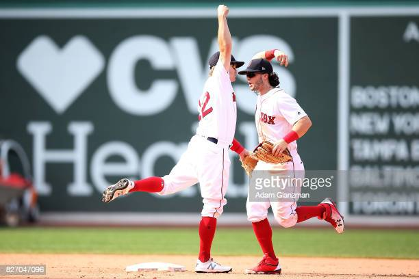 Andrew Benintendi and Brock Holt of the Boston Red Sox recat after a victory over the Chicago White Sox at Fenway Park on August 6 2017 in Boston...