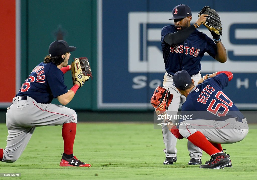 Andrew Benintendi #16, Jackie Bradley Jr. #19 and Mookie Betts #50 of the Boston Red Sox celebrate after defeating the Los Angeles Angels in the ninth inning at Angel Stadium of Anaheim on July 21, 2017 in Anaheim, California.