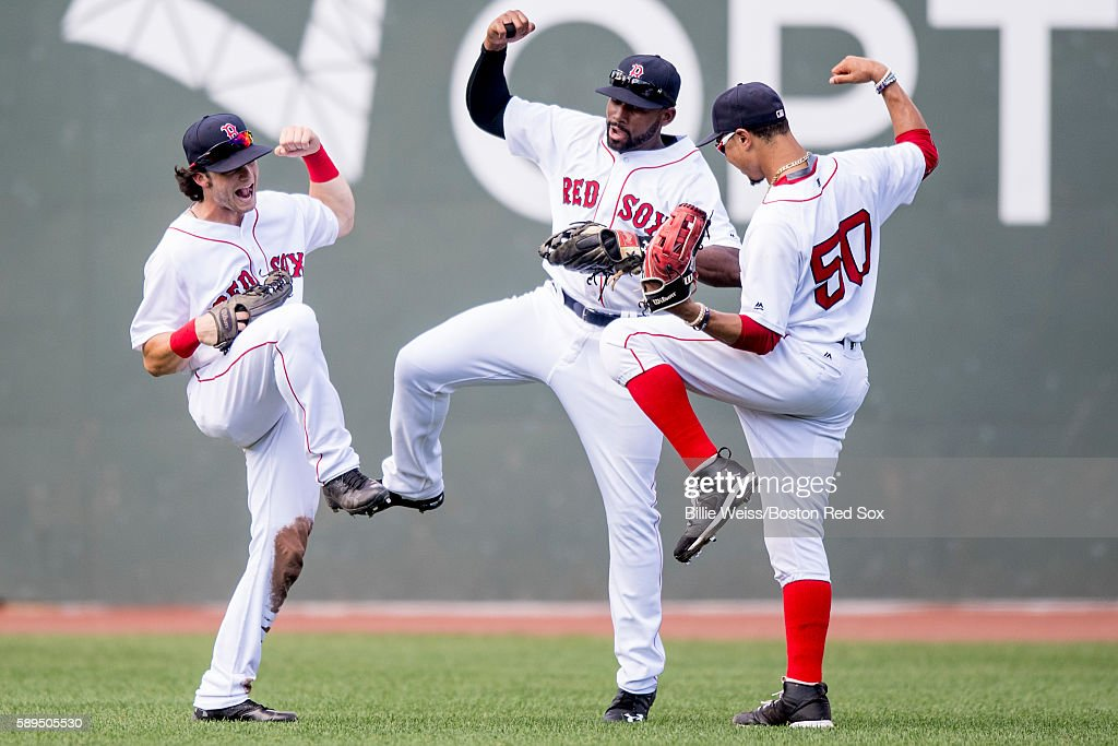 Andrew Benintendi #40, Jackie Bradley Jr. #25, and Mookie Betts #50 of the Boston Red Sox celebrate a victory against the Arizona Diamondbacks on August 14, 2016 at Fenway Park in Boston, Massachusetts.