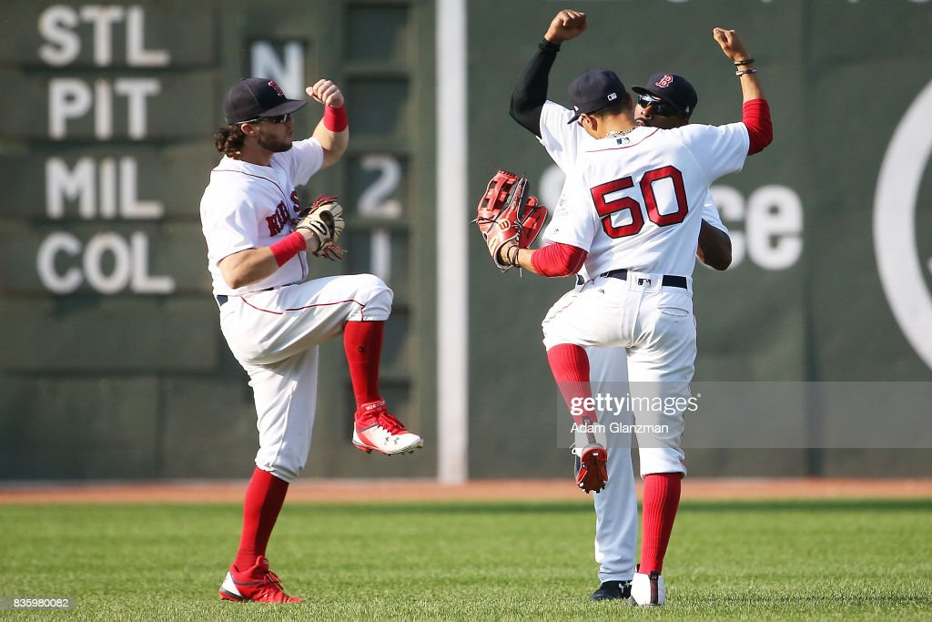 Andrew Benintendi #16, Mookie Betts #50 and Jackie Bradley Jr. #19 of the Boston Red Sox react after the victory over the New York Yankees at Fenway Park on August 20, 2017 in Boston, Massachusetts.