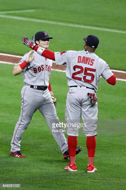 Andrew Benintendi of the Boston Red Sox and Rajai Davis celebrate the Red Sox 108 eleven inning win over the Baltimore Orioles at Oriole Park at...
