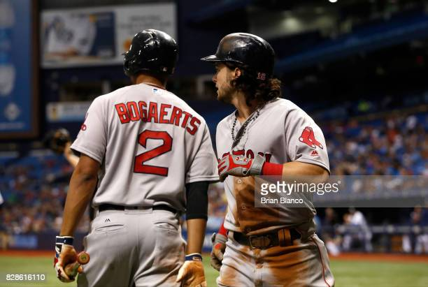 Andrew Benintendi of the Boston Red Sox celebrates with teammate Xander Bogaerts after scoring off the error by pitcher Jake Odorizzi of the Tampa...