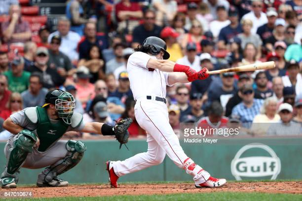 Andrew Benintendi of the Boston Red Sox hits a double during the fourth inning against the Oakland Athletics at Fenway Park on September 14 2017 in...